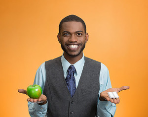 Portrait young, fit, happy executive man holding green fresh apple in one hand, pills, vitamins in another. Sugar free chewing gum, dentist recommended. Face expressions, emotion, health care. Dieting